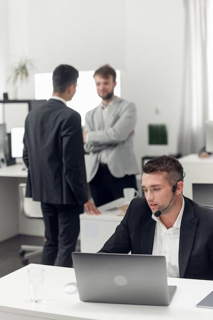 Een makelaar op de werkplek van het agentschap onderhandelt met de klant via internet en telefoon Premium Foto