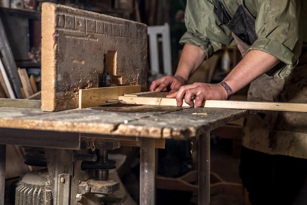 Een man aan het werk met houtproduct op de machine Gratis Foto