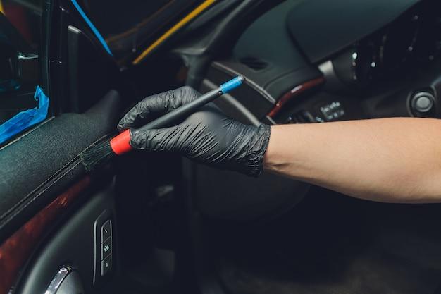 Een man auto met doek en borstel schoonmaken. auto detaillering. Premium Foto