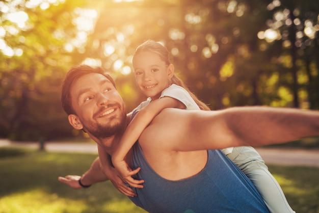 Een man berijdt een meisje op zijn schouders in het park. Premium Foto
