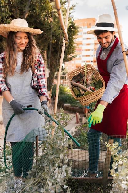Een man die de glimlachende vrouwelijke tuinman leidt die de plant water geeft met een groene slang Gratis Foto
