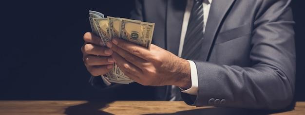Een man die dollargeld in een privéruimte, panoramische banner telt Premium Foto