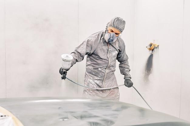 Een man die een auto schildert Premium Foto