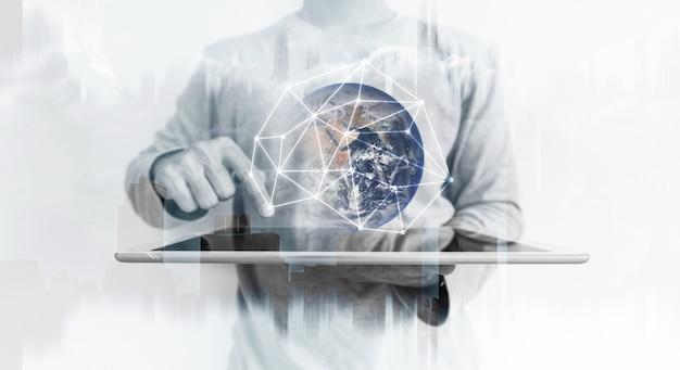 Een man die een digitale tablet gebruikt met een wereldwijd hologram voor netwerkverbindingstechnologie. Premium Foto