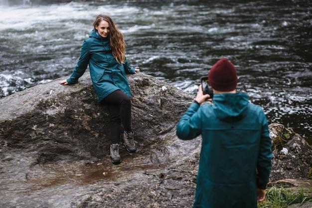 Een man die foto's maakt van zijn vrouw op zijn telefoon tegen de achtergrond van een waterval Premium Foto