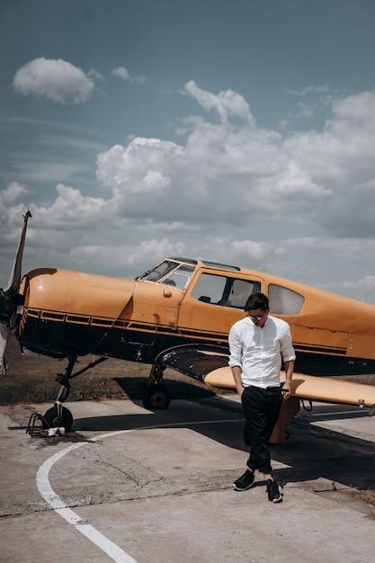 Een man die op de achtergrond van een klein motorvliegtuig staat. Gratis Foto