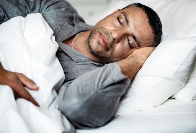 Een man die op een bed slaapt Premium Foto