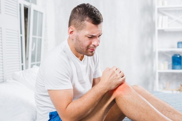 Een man die zijn knie aanraakt met twee handen die ernstige pijn hebben Gratis Foto