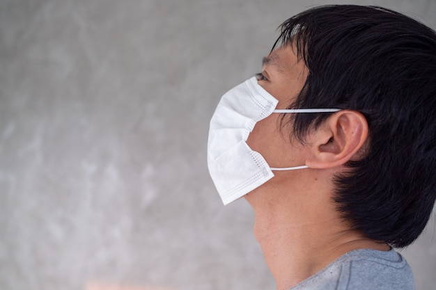Een man draagt een masker om het covid-19-virus dat zich over de hele wereld verspreidt te voorkomen of pm2.5 te voorkomen. iedereen moet de handen ineen slaan om de dodelijke infectie te stoppen. Premium Foto