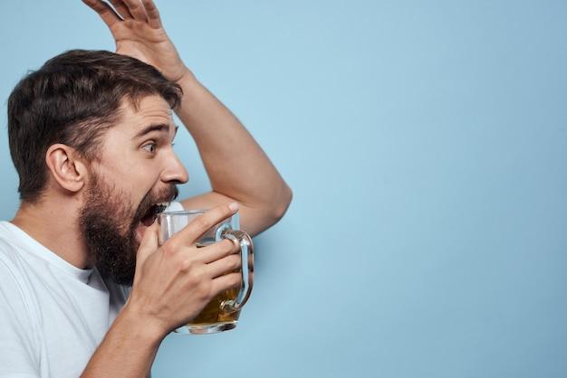 Een man drinkt bier uit een glas en eet junk fried fast food Premium Foto