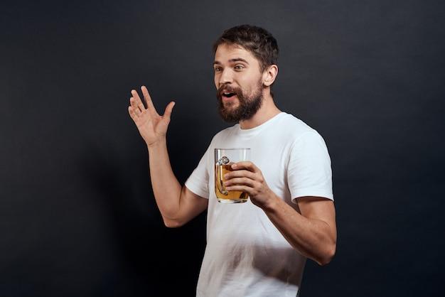 Een man drinkt bier uit een glas en eet junk-gefrituurd fastfood Premium Foto
