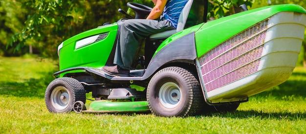 Een man en een grasmaaier. lange banner Premium Foto