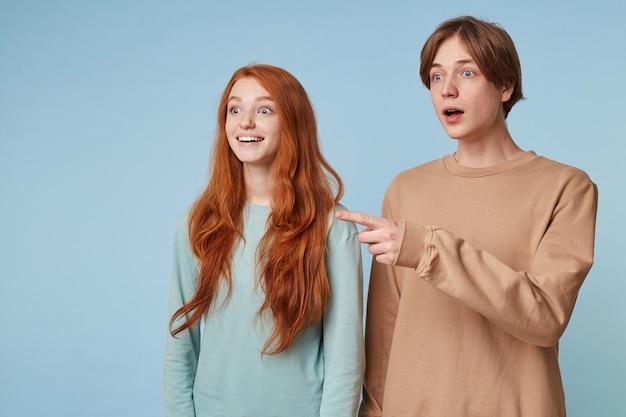 Een man en een roodharige vrouw staan opzij en kijken gefascineerd door de indruk Gratis Foto
