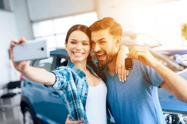 Een man en een vrouw doen selfie in de buurt van hun nieuwe auto. Premium Foto
