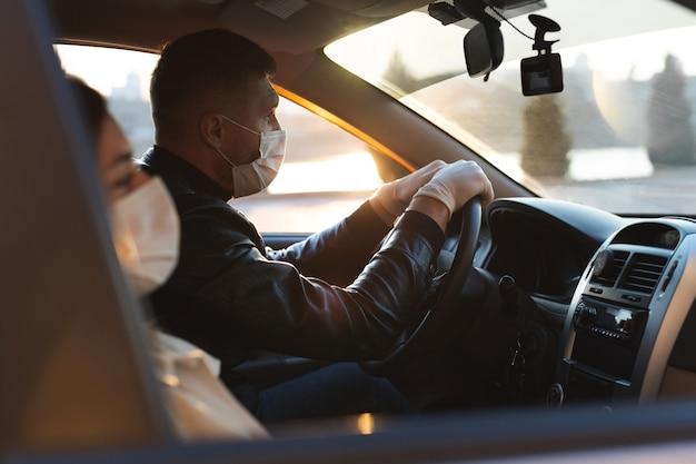 Een man en een vrouw dragen medische maskers en rubberen handschoenen om zichzelf te beschermen tegen bacteriën en virussen tijdens het autorijden. gemaskerde mannen in de auto. coronavirus (covid-19 Premium Foto