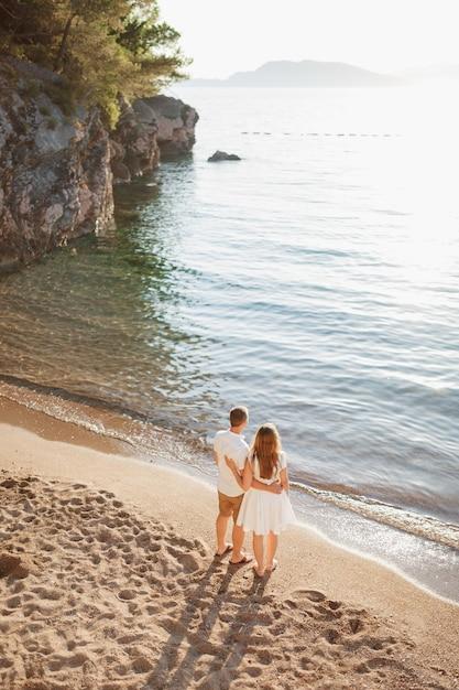 Een man en een vrouw omhelzen elkaar op de oever van een kalme zee en kijken in de verte Premium Foto