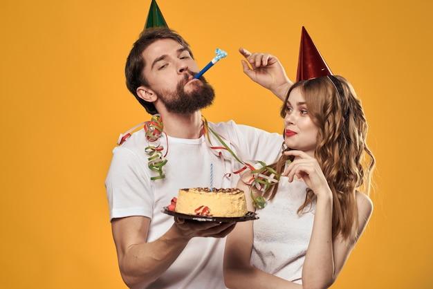 Een man en een vrouw op een verjaardag met een cupcake en een kaars in een feestelijke pet hebben plezier en vieren samen de vakantie, gelukkig paar Premium Foto