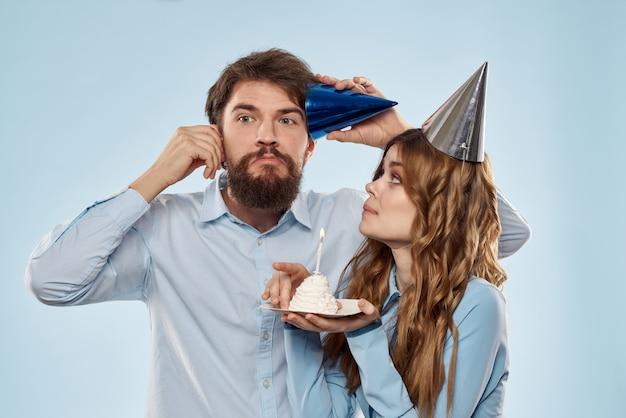 Een man en een vrouw op een verjaardag met een cupcake en een kaars in een feestelijke pet hebben plezier en vieren samen de vakantie Premium Foto