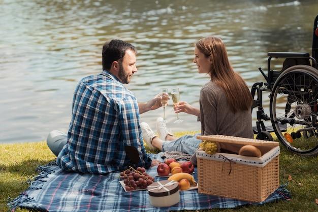 Een man en een vrouw zitten op de oever van het meer Premium Foto