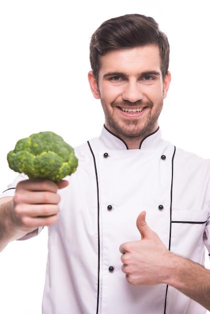 Een man houdt broccoli in zijn hand en vertoont een superteken. Premium Foto