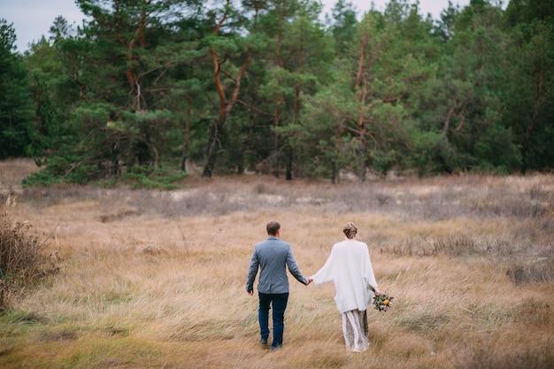 Een man houdt de hand van een vrouw vast op de achtergrond van een bos Premium Foto