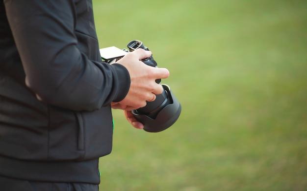 Een man houdt een camera in zijn handen op een wazige groene achtergrond Premium Foto