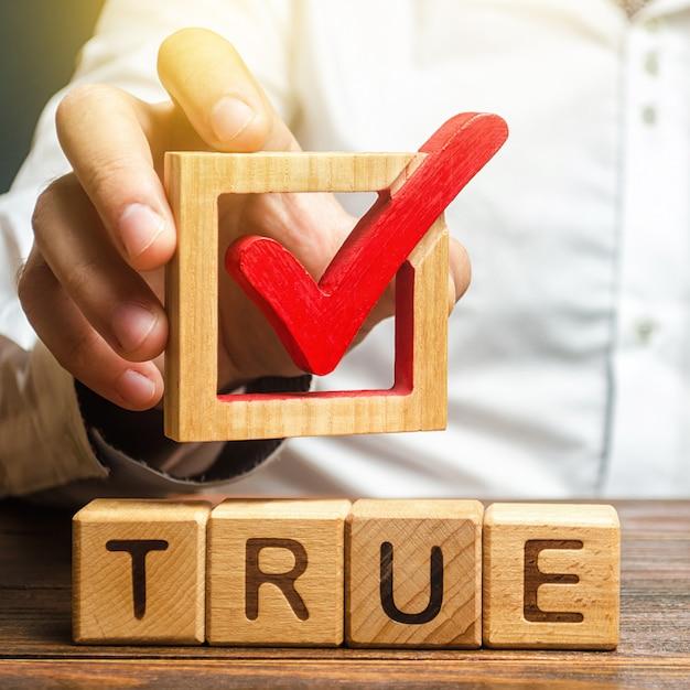 Een man houdt een rood vinkje boven het woord waar. bevestig de waarheid en waarheid. vecht tegen nepnieuws Premium Foto