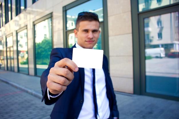 Een man houdt een visitekaartje voor zich copyspace Premium Foto