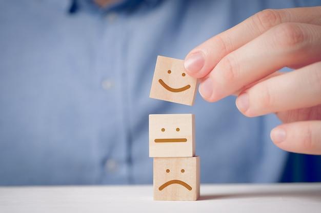 Een man houdt met zijn vingers een houten kubus vast met een positief gezicht naast een ontevreden en neutrale. voor het evalueren van een actie of resource. Premium Foto