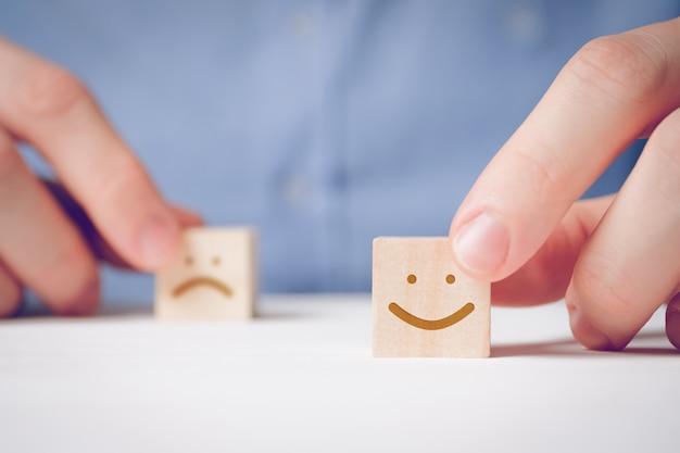 Een man houdt met zijn vingers een houten kubus vast met een positief gezicht naast een ontevreden. voor het evalueren van een actie of resource. Premium Foto