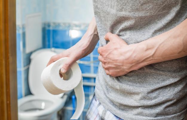 Een man houdt toiletpapier vast. het concept van diarree. aambeien. Premium Foto