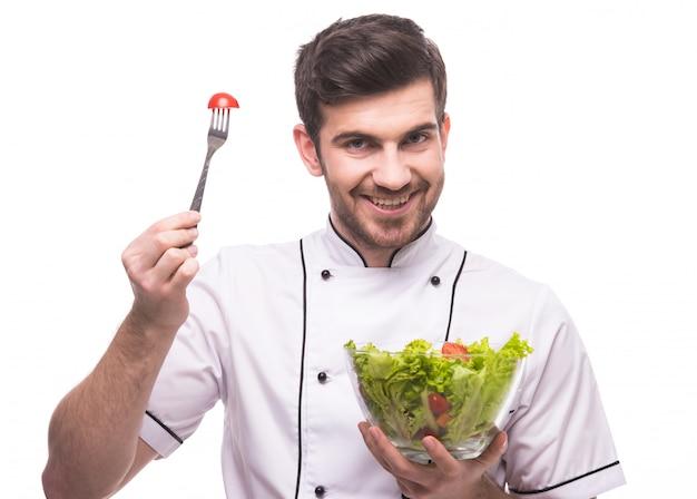 Een man in de kleding van een kok proeft een salade. Premium Foto