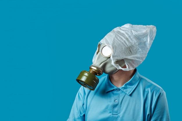 Een man in een gasmasker en een plastic zak op zijn hoofd symboliseert de bescherming van het milieu tegen vervuiling op blauw Premium Foto