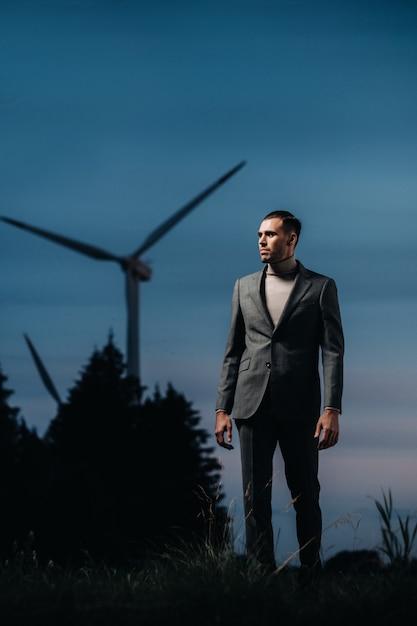 Een man in een grijs pak staat naast een windmolen na zonsondergang. zakenman in de buurt van windmolens bij nacht. modern concept van de toekomst. Premium Foto