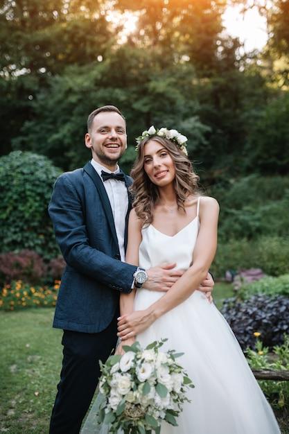 Een man in een pak knuffelen zijn vriendin buitenshuis, de bruid en bruidegom op zijn trouwdag Premium Foto