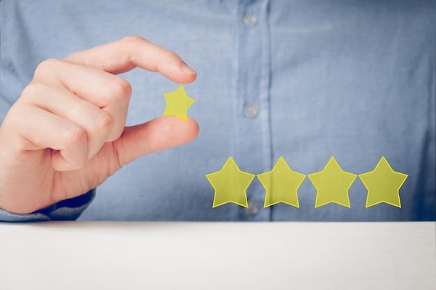 Een man in een shirt wil abstract een vijfsterrenclassificatie op zijn handen leggen. beste score Premium Foto