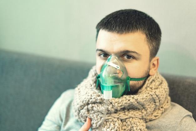 Een man in een warme sjaal en een groen inhaleermasker Premium Foto