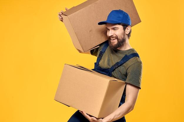 Een man in een werkend uniform met pakketten op een gele achtergrond. Premium Foto