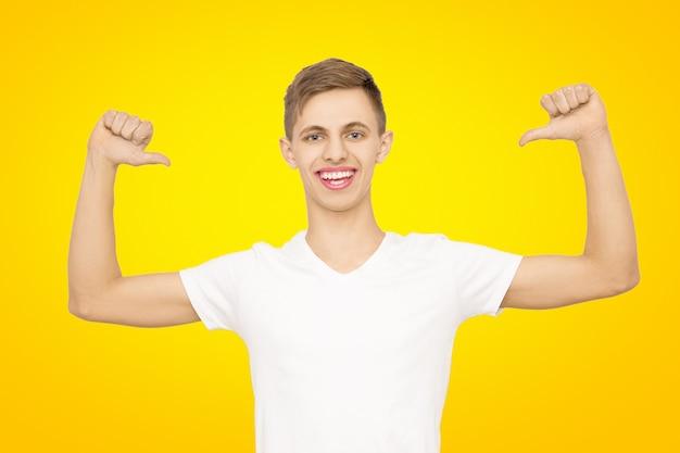 Een man in een wit t-shirt met zijn handen omhoog in de studio op een gele, isolaat Premium Foto
