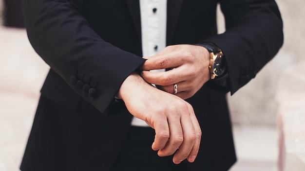Een man in een zwart pak strekt zijn mouwen Premium Foto
