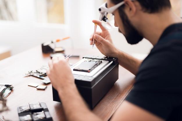 Een man in speciale bril houdt een schroevendraaier in zijn hand. Premium Foto