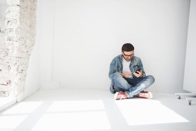 Een man in vrijetijdskleding zit thuis in een leeg appartement met een creditcard Gratis Foto