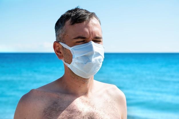 Een man in wit medisch masker aan zee Gratis Foto