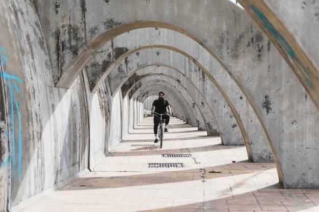 Een man in zwarte kleding die de fiets in overwelfde galerij berijdt Gratis Foto