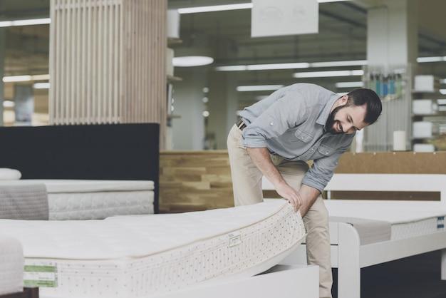Een man inspecteert een matras in een matraswinkel. Premium Foto