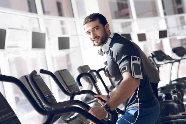 Een man is aan het oefenen op een loopband in een moderne sportschool. Premium Foto