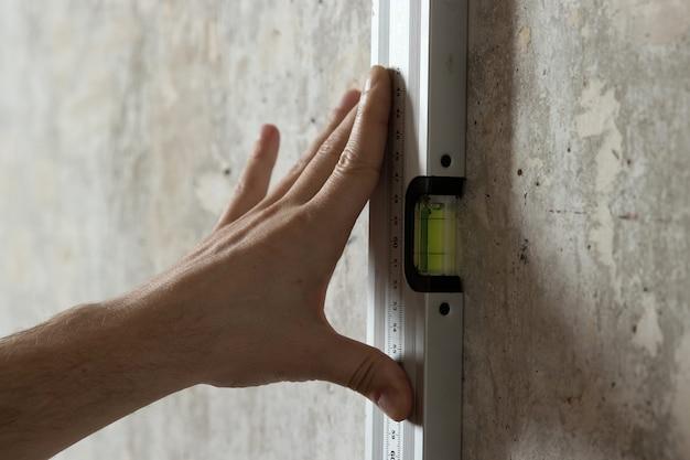 Een man meet aan de muur met een liniaal Premium Foto