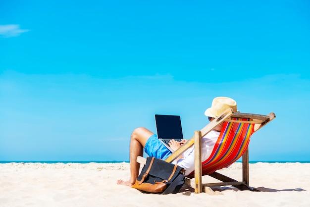 Een man met behulp van laptop op het tropische strand op vakantie. Premium Foto