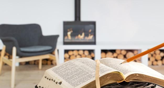 Een man met een bijbel met een potlood, tegen de achtergrond van de woonkamer met een open haard. een boek lezen in een gezellige omgeving. Gratis Foto