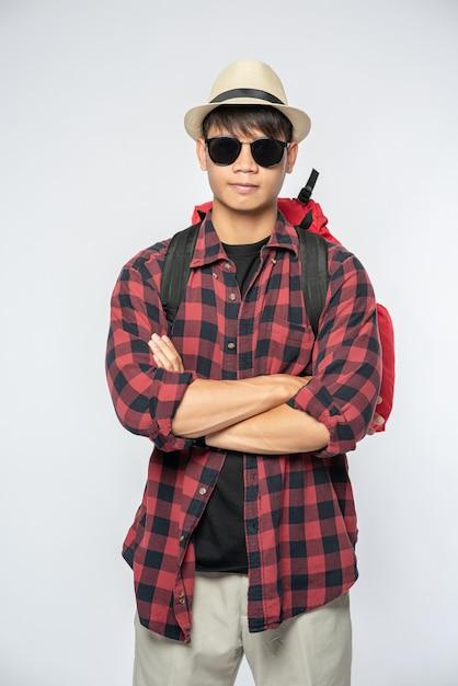 Een man met een bril gaat op reis, draagt een hoed en draagt een rugzak Gratis Foto